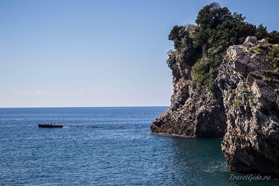Лодка в море у скалы
