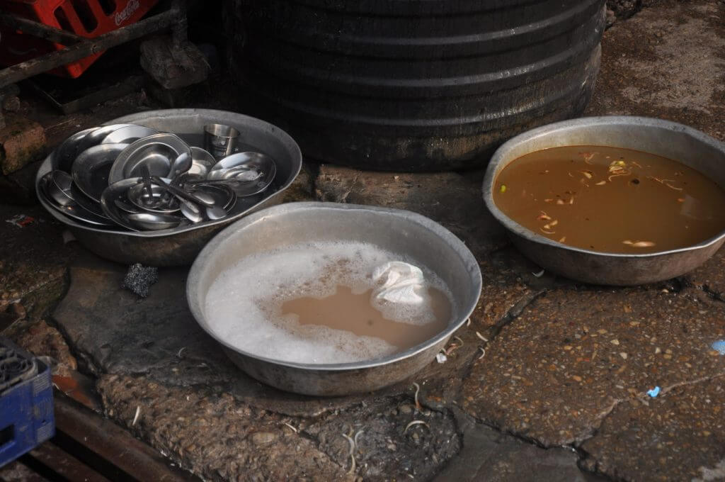 Мытьё посуды на улице у кафе в Индии