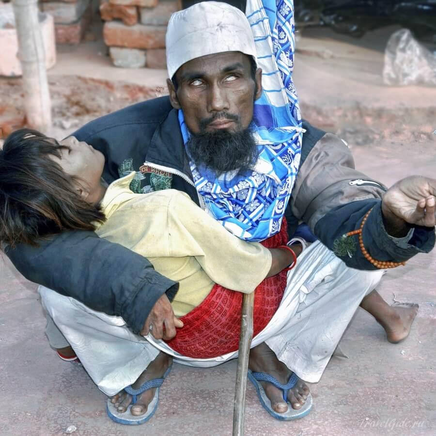 Слепой попрошайка с девочкой на руках в дели Индия