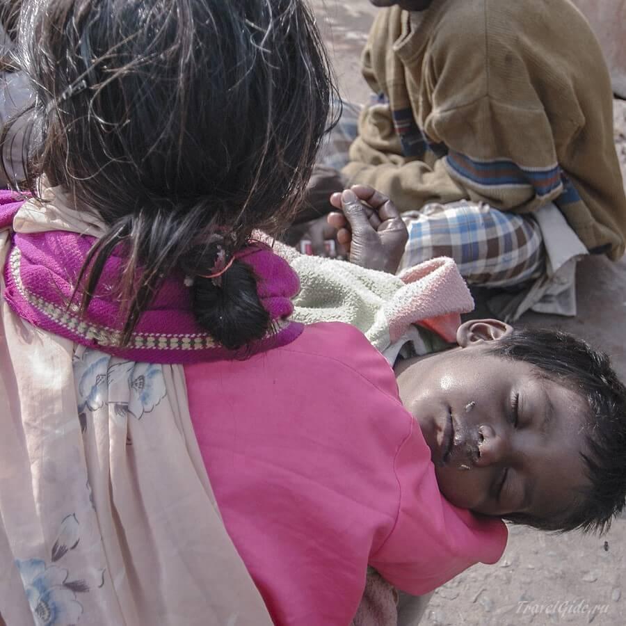 Попрошайка со спящим мальчиком на руках