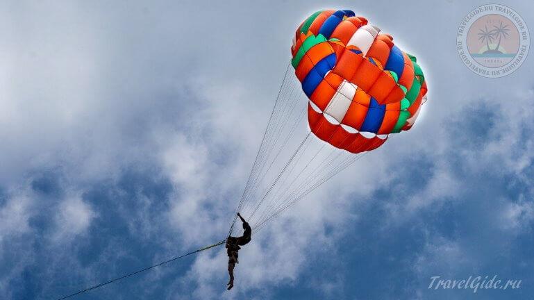 Полёт на парашюте в небе над пляжем